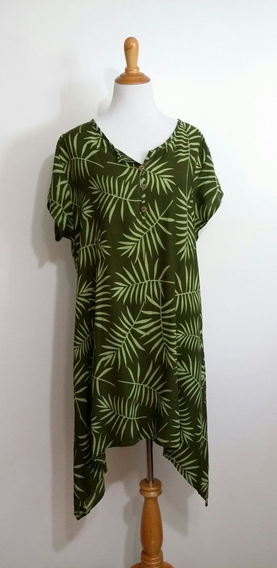 This is a very cool palm leaf dress with a hi lo hem and a loose, drapey fit. The dress has short sleeves and a button front and can be worn as a dress or it also makes a great tunic. This green on green print would look great with an exotic statement necklace in wood or gold and either flats or platform sandals.  Tropical green tunic dress rayon hilo hem short sleeves partial button front size L, XL, plus size measures: 44 bust 46 waist free hips 35 long at shortest point mint condition