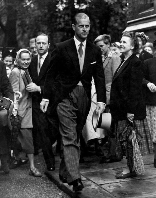 Prince Philip , Duke of Edinburgh;1952. Sensing the camera's intrusive eye the Duke looks characteristically impatient. The woman on the right gazes at him enraptured - and she wasn't the Duke's only fan.