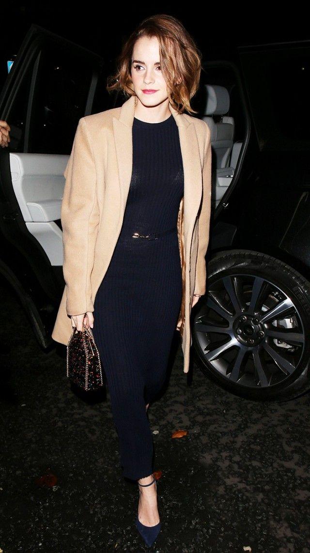 Emma Watson wears a long ribbed dress, ankle-strap heels, a camel coat, and mini Stella McCartney bag