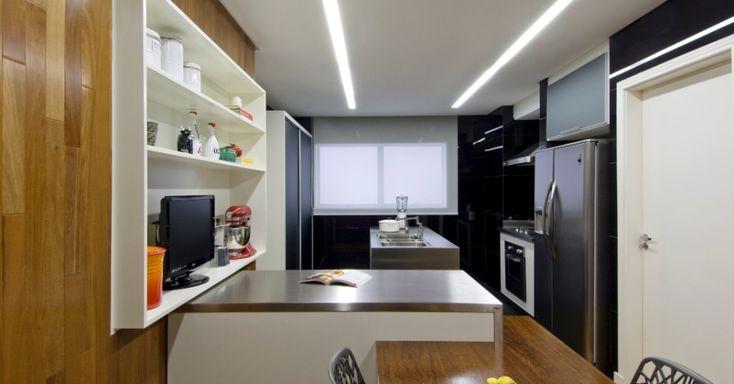 """A cozinha estreita e comprida está divida em área de trabalho (fundos) e copa (primeiro plano). O piso de cumaru (Indusparquet) """"sobe pelas paredes"""". Para quebrar a monotonia da madeira, o preto do Revest Glass, revestimento composto por um sanduíche de vidro """"recheado"""" por tinta. """"Rasgos de luz"""" no gesso levam lâmpadas fluorescentes fechadas por um material acrílico leitoso que diminui ofuscamento. O apartamento no Itaim Bibi, em São Paulo, foi reformado pelo escritório Sidney Quintela…"""