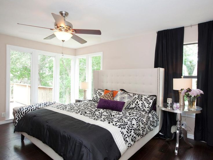 A black and white palette in this bedroom gets small punches of color from purple pillows and fresh flowers. A trio of large windows and French doors are left uncovered to keep the room from looking dark.