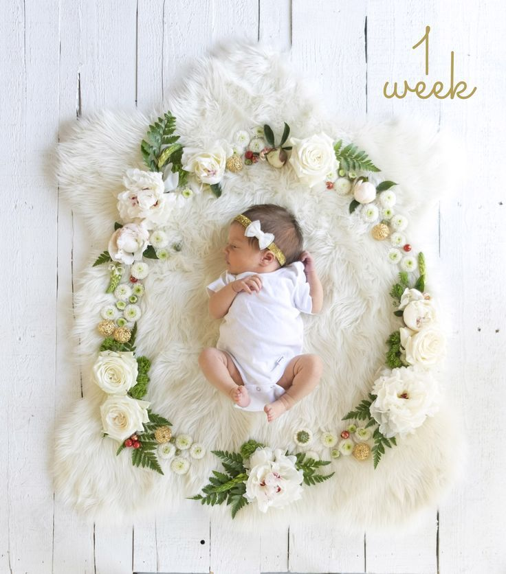 Newborn baby girl floral picture. One week. Fresh flowers