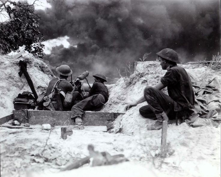 Machine gunners of the 18th Infantry Brigade, 7th Australian Division fire a Vickers heavy MG at the Japanese in Balikpapan on the island of Borneo. Note the flame thrower firing from a position next to the Vickers.