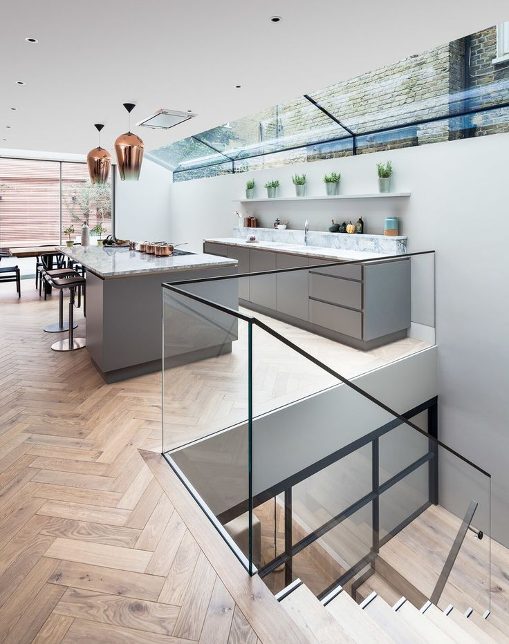 Kitchen and stairs down to basement. Glass balustrade, open plan and timber parquet flooring. Finch House, 2016