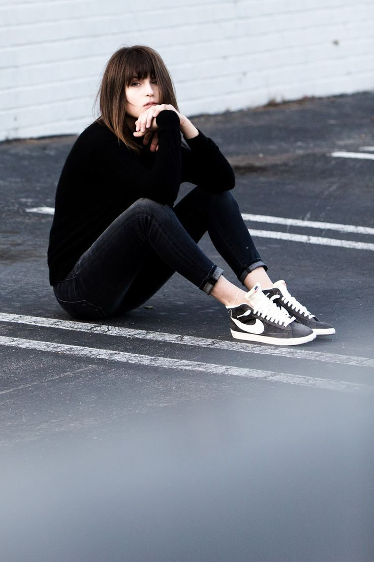 Mid length brunette hair, roll neck jumper, cropped black jeans, Nike trainers