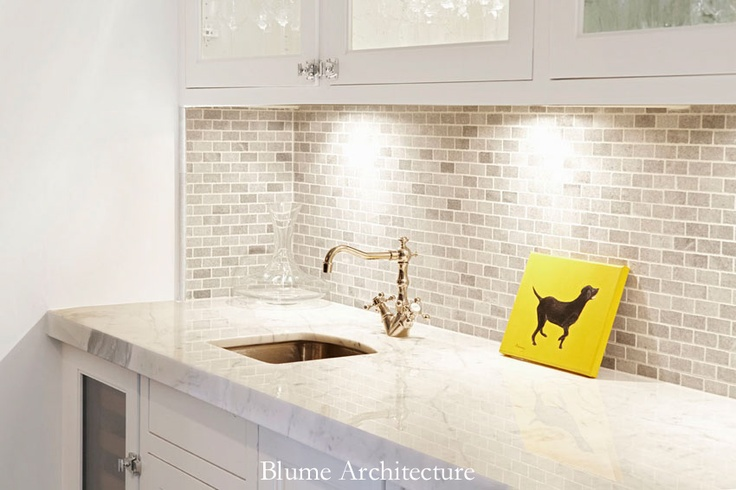 stone backsplash. sink. white kitchen. classic. glass cabinets