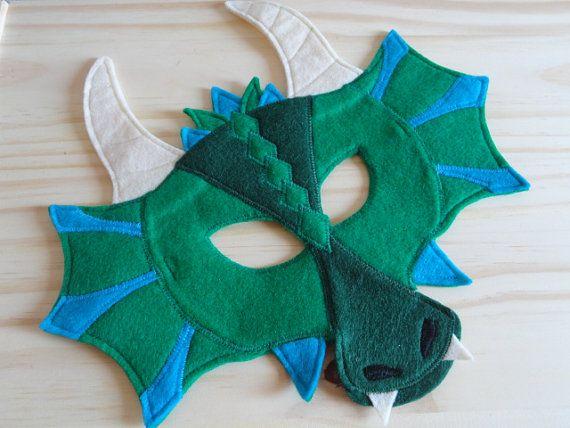 Lassen Sie Ihren kleinen zu tun, um eine mutige und mächtigen Drachen in dieser Art handgemachte Filz Maske. Die abgebildete Maske besteht aus einer reichen grünen Öko-Filz mit dunklen Grün und Türkis Akzente und Creme Hörner und Zähne. Gibt es ein Gummiband für einfach bequem tragen.