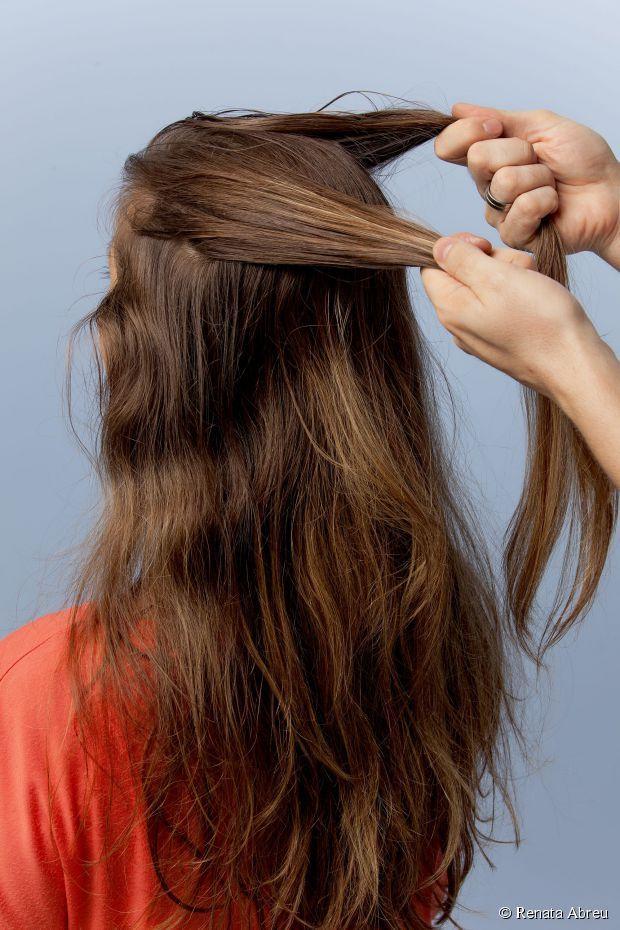 3 - Separe duas mechas dos cabelos da parte de cima da cabeça, puxando da franja para trás;
