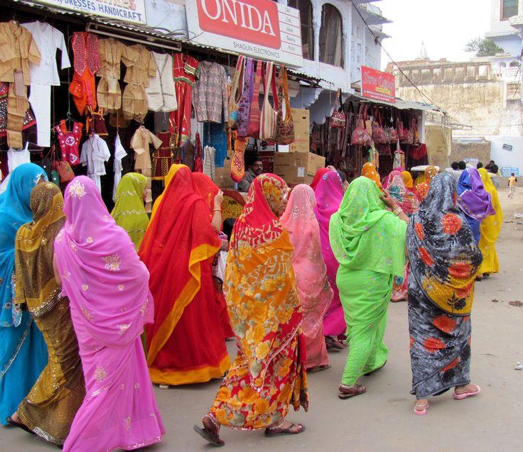Women dressed in colorful saris walking through the village, India.