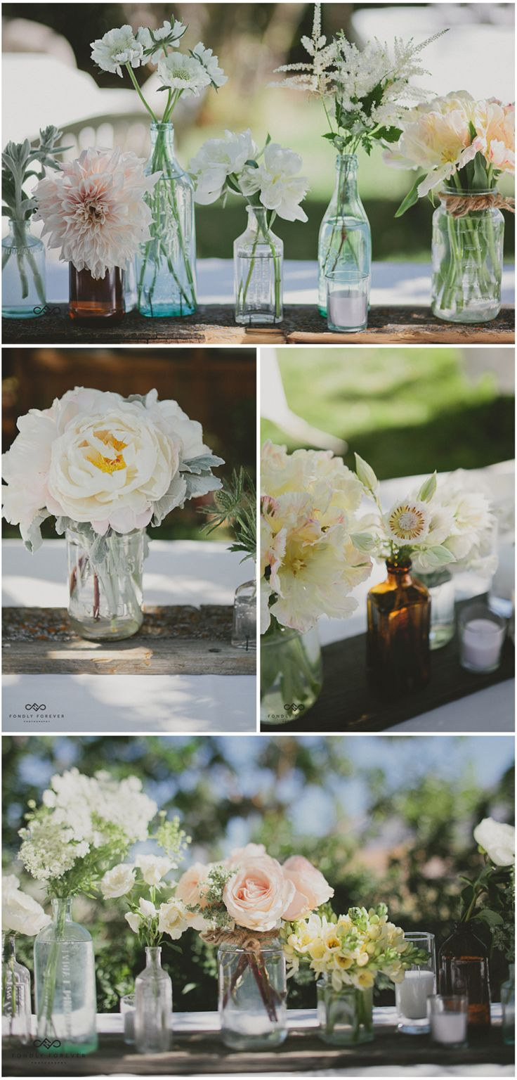 Pretty flowers in different glass jars and bottles