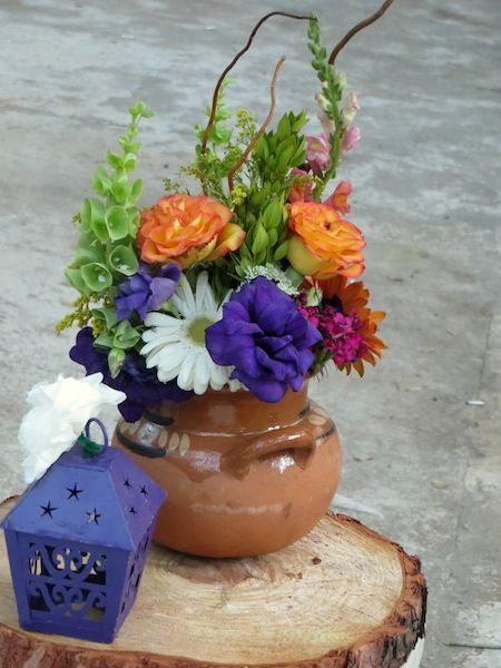 DIY centerpieces for a Mexican fiesta or wedding - love the colorful flowers and the use of this Mexican olla (bean pot). The carved tree bark is also great for displaying the centerpieces!