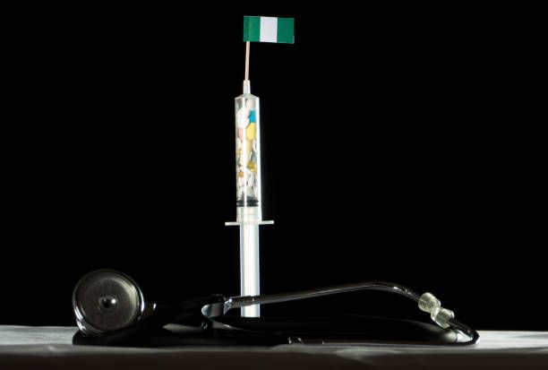 stethoscope and syringe filled with drugs injecting the nigerian flag