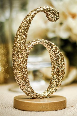 Glitter decorations, like this gold table number, are essential to fabulous wedding day.