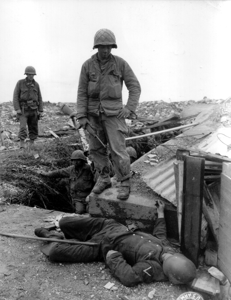 GIs of the 79th Infantry Division after the battle in the environs of the port city of Cherbourg, France, June 1944. Visible in the trench is a medic helping the wounded. The German corporal on the ground was among the unlucky ones.