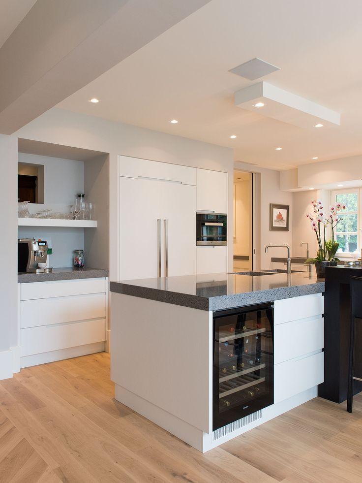 Modern en toch enigszins tijdloos. Deze ruime, witte keuken is geheel greeploos en daardoor erg gebruiksvriendelijk. Gezinskeuken dankzij de bar die vast zit aan de keuken en helemaal compleet dankzij de prachtige wijnkoeling.