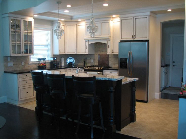I don't really like the black and white mixed cabinets -- it should be one or the other -- but I like the style of the island: counter space with a raised bar.  #kitchen