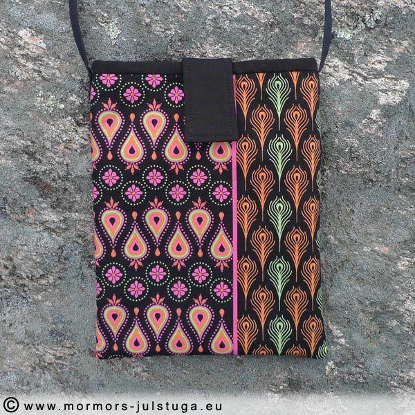 Liten praktisk väska för mobil, plånbok mm. Svart med starka färger, fodret svart. Stängning med kardborre Tyget är av bomull.  Mått 23 x 18,5 cm. Rem 109 cm.