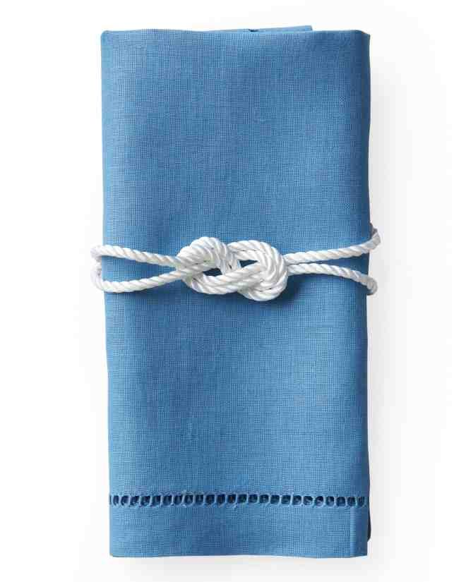 Give napkins at your table settings aGilligan-inspiredtouch. Double up a length of cord (mjtrim.com), hold it in the middle, and tie an 8-knot. Place knot on a folded napkin; wrap ends around. Trim and secure with white gaffer's tape.Watch Our 8-Knot How-To Video