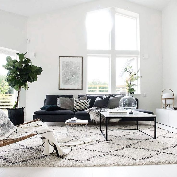 Scandinavian style living room with clean white walls, grey sofa, geometric rug and indoor plants