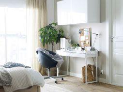Dormitorio con escritorio blanco, silla giratoria negra con ruedas y un armario de pared.