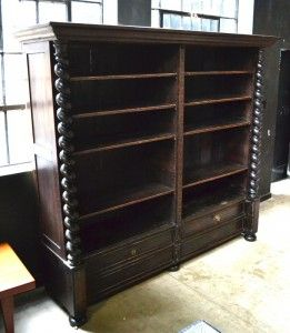 Africa then & now - Provenance Auction House: A Massive 19th C Oak Bookcase. Straight pediment, above a bouble row of shelving, central carved upright, sides flanked with ebonised barley twist columns, shelves having a pair of matching drawers, all set upon bun feet. 2140 x 2340 x 600mm.