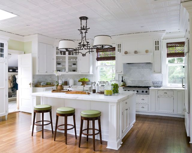 Carrara / White Kitchen...with a splash of green apple and bronze. I just wish it had a full size range instead of a topper. Overall, nice layout and use of wall space.