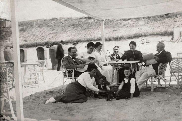 Strandleven. Gedistingeerd geklede dames en heren met kinderen van de familie O: W: zitten onder een luifel op het strand aan rieten tafels met stoelen thee te drinken en kranten en tijdschriften te lezen .