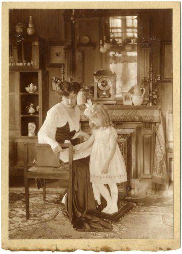 Interieurs. Portret van een moeder, zittend op een stoel (zonder rugleuning), met een meisje staand naast haar. Het meisje wijst naar in het boek dat op de schoot van de moeder ligt. De moeder is gekleed in een lange jurk in lichte en donkere stoffen en een sleepje aan de achterzijde. De jurk heeft een lage hals en driekwart mouwen. Het meisje draagt een wit jurkje en een witte strik in haar blonde, krullende haren. Achter hen is een (dichte) haard te zien, met daarboven een…