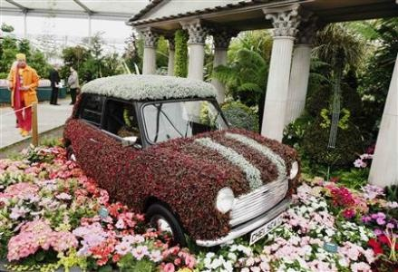 A man passes a mini covered in flowers on the Birmingham City Council stand during the press day at the Chelsea Flower Show in London May 21, 2012. REUTERS-Luke MacGregor