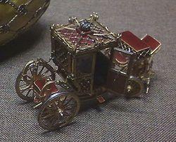 1897 - Uovo dell'incoronazione - sorpresa. - Modellino lungo 9,4 cm. della carrozza usata per l'incoronazione. Materialioro, platino, smalto rosso fragola, diamanti, rubini, cristallo di rocca