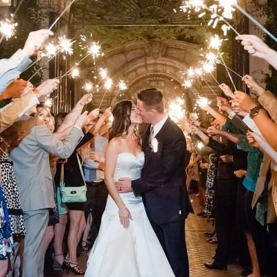 couple shares a final wedding day kiss at their sparkler send off leslie ann photography