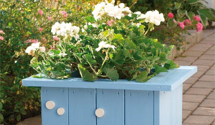 En blomsterkasse med stående bord må ha en ramme oppe og nede som bordene festes til. Denne kassa er laget med undervanning av lecakuler. En enkel dekorasjon gir den et personlig preg.