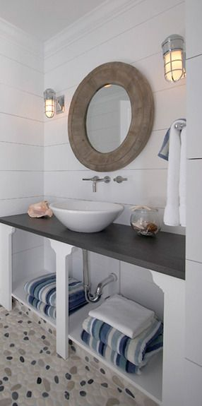 What a great coastal inspired bathroom!  This is a great bathroom to inspire those memories from the beach.  This white vessel sink paired with an out of the wall faucet is great!  The nautical looking sconces make this bathroom a success!  Love the play between the pebble floors, wooden mirror and spectacular lights!