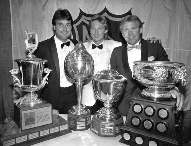 Edmonton Oilers Paul Coffey, left, Wayne Gretzky and coach Glen Sather pose with the four awards they picked up at the annual NHL Awards in Toronto on June 10, 1986.