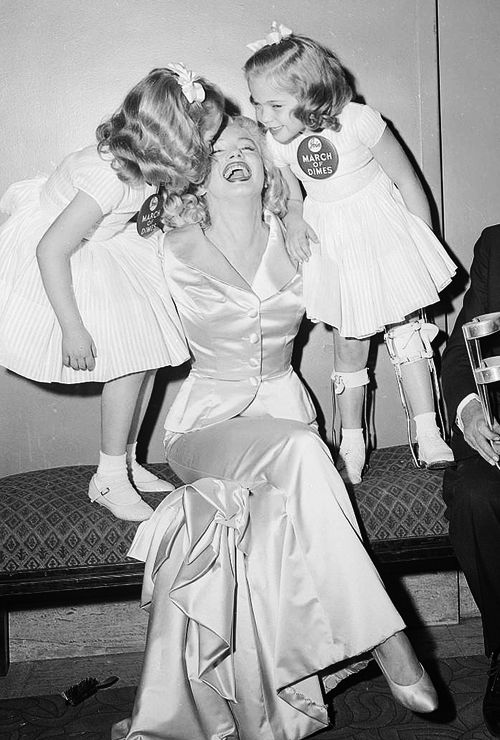 Marilyn Monroe receiving kisses at the March of Dimes charity event <3 1958.