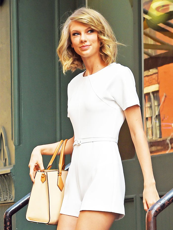 Taylor Swift in a white jumpsuit and tan purse