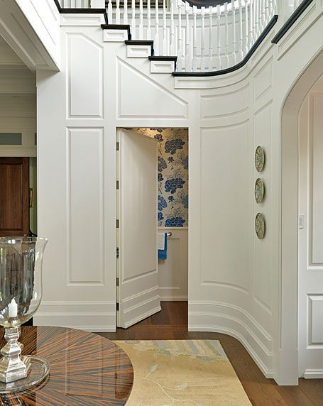 Curved staircase wall with hidden door leading to powder room.