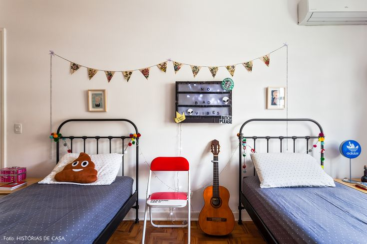 quarto de criança com camas de ferro pintadas de preto e muitos acessórios coloridos