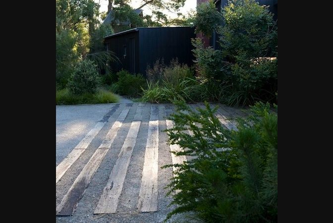 exterior charcoal/black lots of coastal greenery and a gravel driveway with second hand sleepers stabilising it