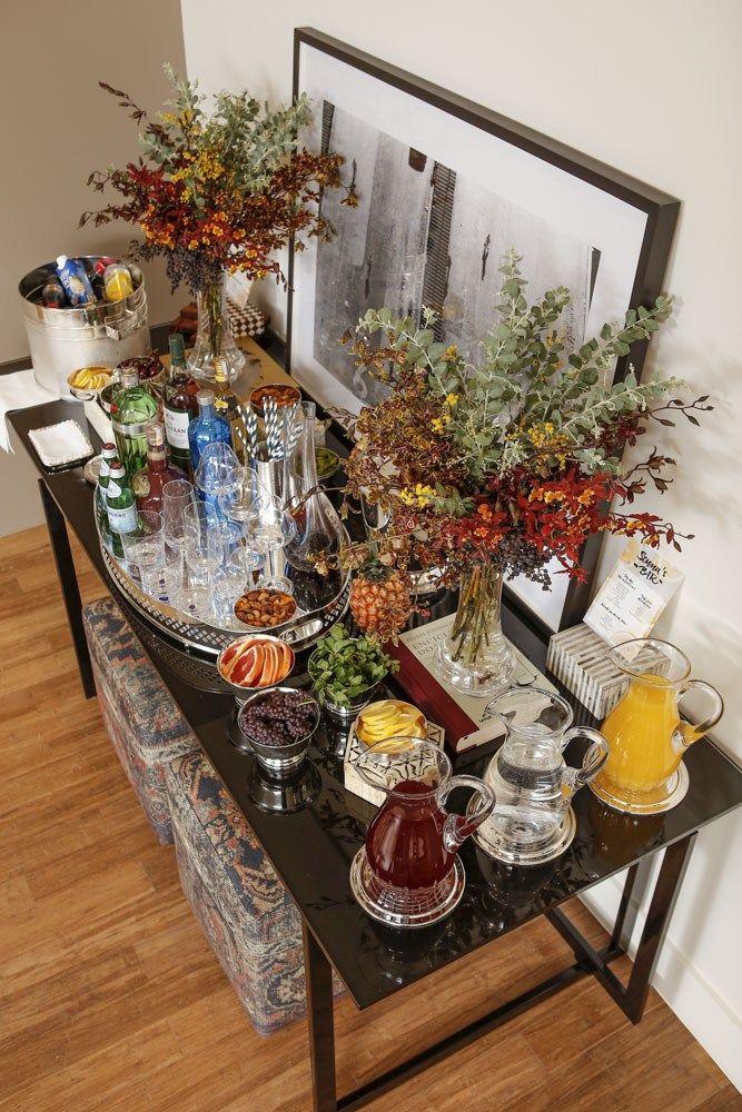 Ao centro de nossa mesa, em uma bandeja em prata da Luxe 4 Home, loja online da marca St. James, dispomos vodka, gin, whisky, vinho, água com gás, copos de whisky e de água, taças de vinho e decanter em cristal transparentes. Também acomodamos um vaso baixo em formato cilíndrico em prata com canudos para os drinks. Em bowls em prata, oferecemos nuts para evitar que o convidado ingira bebida alcoólica com o estômago vazio.