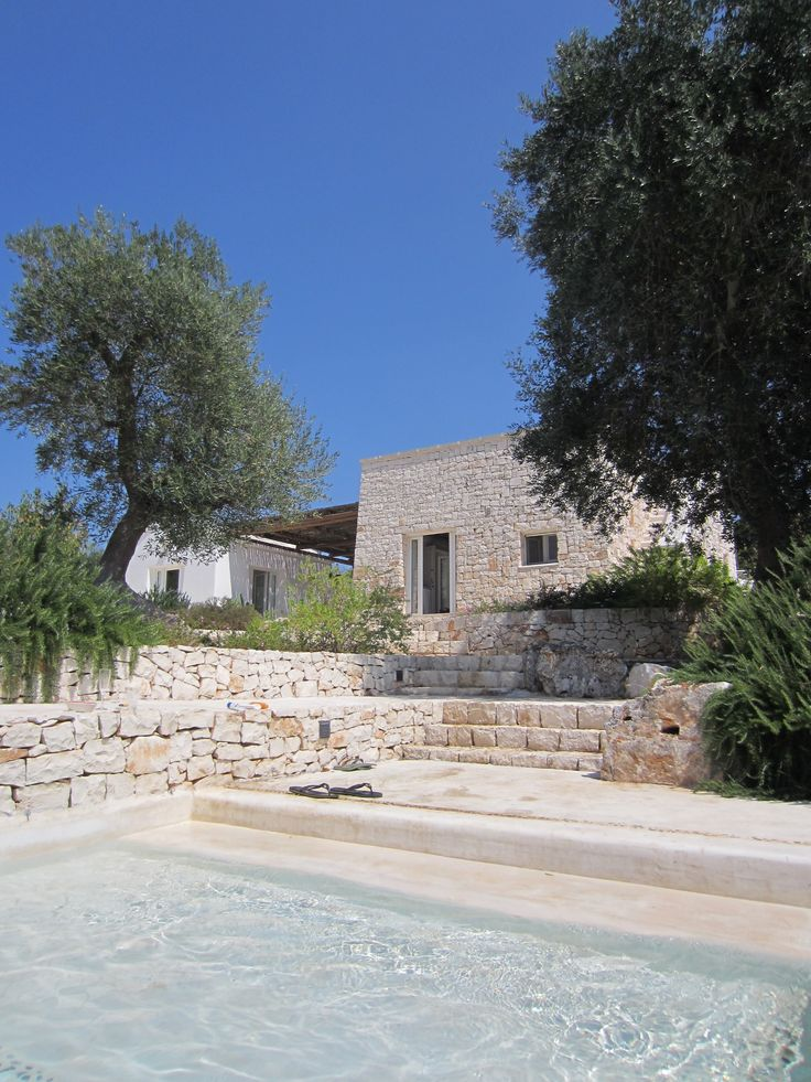 Trullo Gioia, in Puglia, Italy. Two 'lamie' structures connected by a pergola ideal for al fresco dining and lounging.