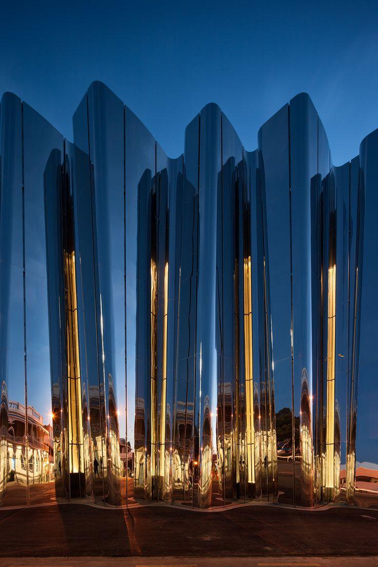 Gaps between the precast panels feature small windows that cast their glow across the facade. Photograph by Simon Devitt.