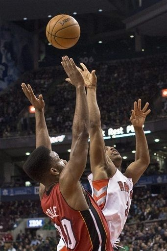 Toronto Raptors' Kyle Lowry, right, battles for the ball with Miami Heat's Norris Cole during first half NBA basketball action in Toronto on Sunday March 17, 2013.