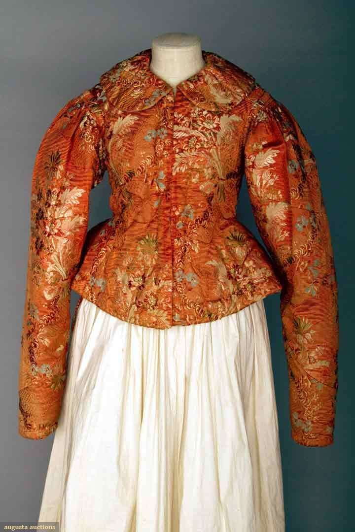"""SILK DUSHEGREYA, GUBERNYA RUSSIA, c. 1800 Lady's jacket made of 18th C ribbed & figured coral silk brocade w/ floral bouquets in blue, green, white & pink, back peplum, round collar, CF steel hooks & eyes, full sleeves taper to wrist, heavily padded & quilted lining, B 35"""", L 19"""", (fading & very minor wear to silk) excellent."""