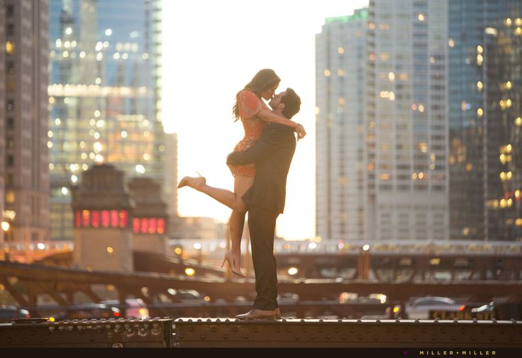 Downtown Chicago riverwalk skyline photos at sunset night engagement photo pictures kissing top of bridge epic skyline