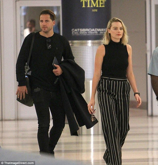 Cute couple! Margot Robbie showed she's all business as she covered up her assets at John F. Kennedy International Airport on Sunday afternoon with husband Tom Ackerley