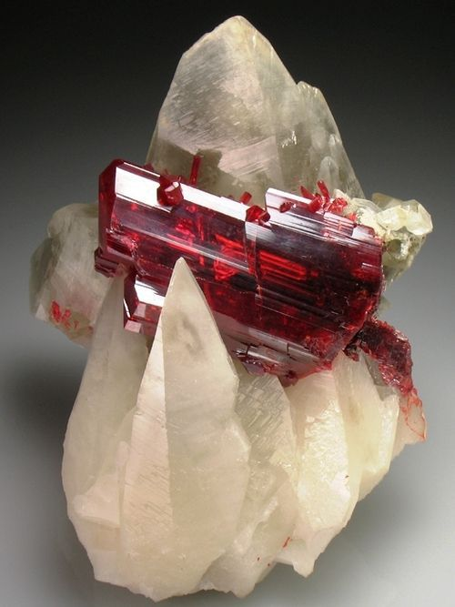 """Realgar (an arsenic sulfide mineral, also known as """"ruby sulphur"""" or """"ruby of arsenic""""):  ruby-red crystals in translucent Calcite scalenohedrons"""
