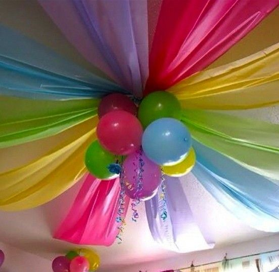 birthday party decor. Take diffrent color table cloths and tape them to to ceiling like that. Then tie 3 diffrent color balloons together and tape them to another set of balloons then tape the all the balloons in the middle of the table cloth.