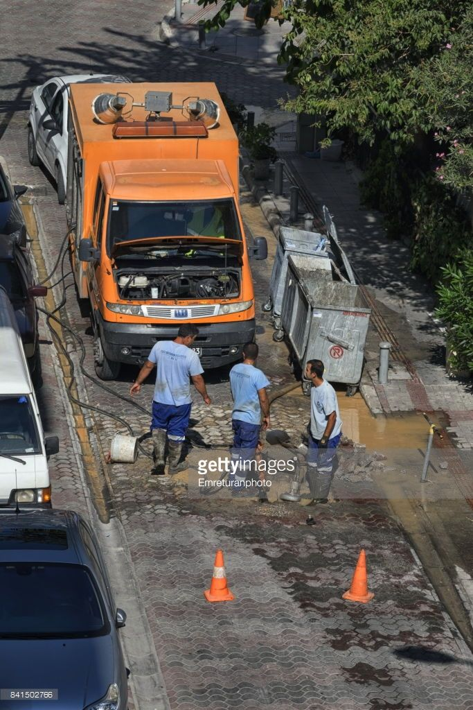 Maintenance team of water department of zmir municipality is fixing a broken water line.Orange colored vehicles are their trademark.