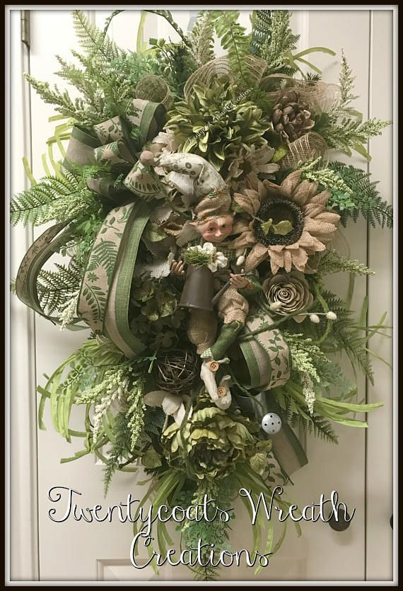 This one of a kind swag will great your visitors in style! This garden elf is on a evergreen wreath base with various florals in burlap and green. He is then layered with ferns, roping, watering can, and a bow and ribbon. The elf is a RAZ elf and is carrying a bronze watering can with flowers and is the focal point of this swag. The swag is approx 40 long from the top to the tip of the fern at the bottom and approx 27 across.  Thank you for visiting Twentycoats where a portion of my sales…